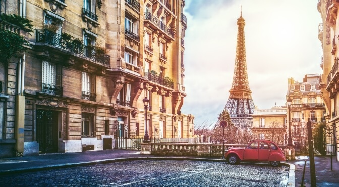 Small red car parked by the Eiffel Tower in Paris